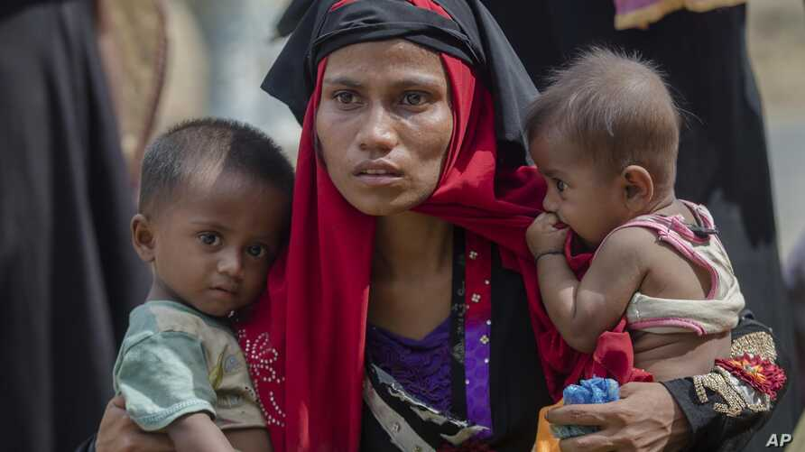 FILE - A Rohingya Muslim woman who crossed over from Myanmar into Bangladesh, holds her son and her daughter, after the government moved them to newly allocated refugee camp areas, near Kutupalong, Bangladesh.
