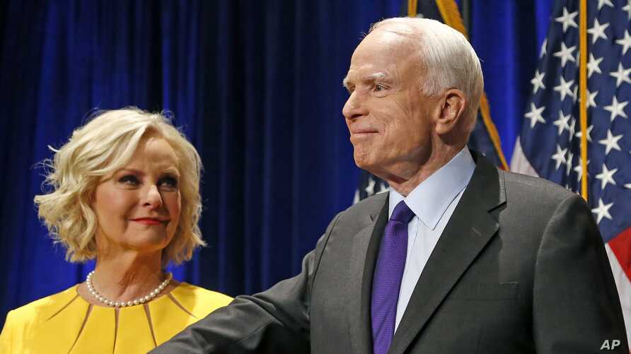 FILE - Sen. John McCain, R-Ariz., right, pauses as his wife, Cindy McCain, looks at him on stage in Phoenix, Nov. 8, 2016.