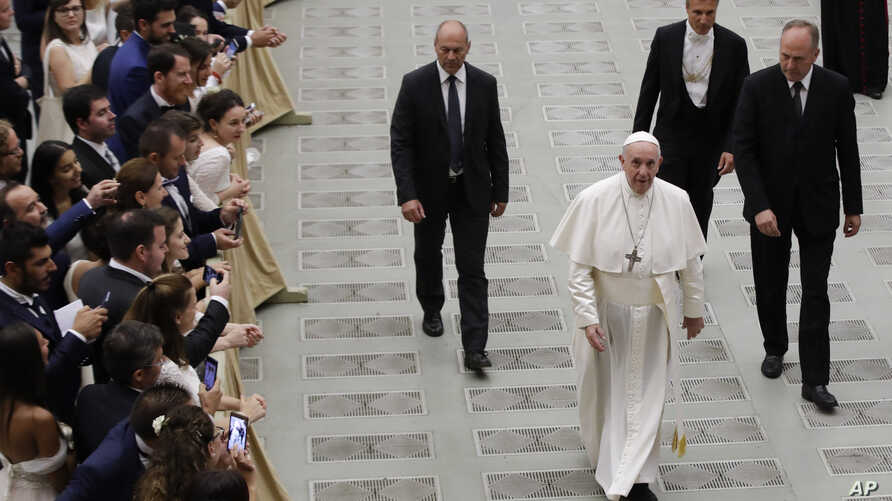 Pope Francis walks in the Paul VI Hall at the end of his weekly general audience at the Vatican, Wednesday, Aug. 21, 2019.