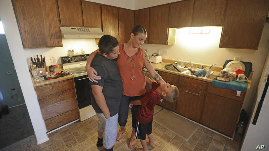 Misty Dotson hugs her son's at their home Tuesday, Aug. 20, 2019, in Murray, Utah. Dotson is a 33-year-old single mother of two boys, ages 12 and 6, who goes to Planned Parenthood for care through the Title X program.