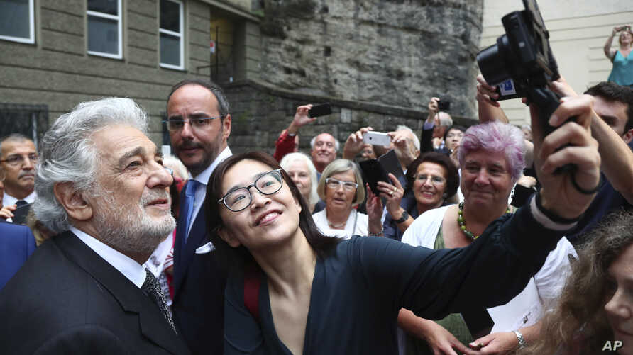 Placido Domingo poses for selfies at the 'Festspielhaus' opera house after he performed 'Luisa Miller' by Giuseppe Verdi in Salzburg, Austria, Sunday, Aug. 25, 2019.