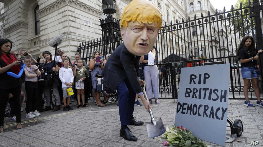 man in a giant Boris Johnson 'head' digs a grave at the foot of a pretend tombstone outside Downing Street in London, Wednesday, Aug. 28, 2019.