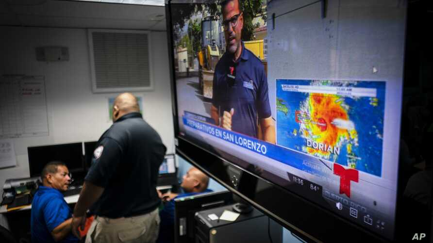 Emergency Center personnel stand next to a tv screen showing a meteorological image of the tropical storm Dorian, as they await its arrival, in Ceiba, Puerto Rico, Aug. 28, 2019.