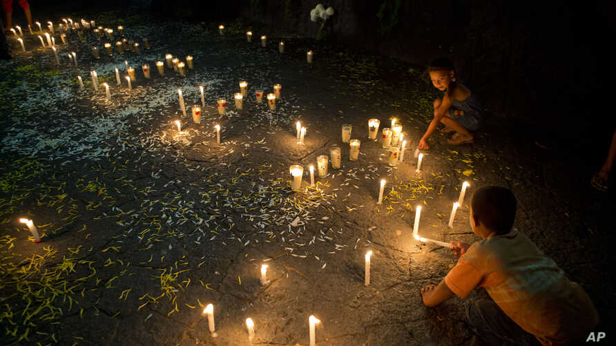 FILE - Children light candles in memory of those killed in clashes with federal forces in the central square of Apatzingan, Michoacan, Mexico, Jan. 7, 2015.