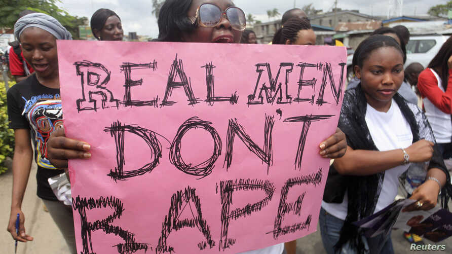 """FILE - A woman carries a placard as she shouts a slogan during the """"Walk Against Rape'"""" procession organized by Project Alert, a"""