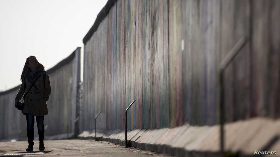 FILE - A woman walks along the former Berlin Wall, now called East Side Gallery, in Berlin March 4, 2013.