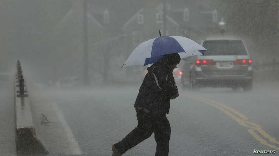 FILE - A man walks in a torrential downpour in Ellicott City, Maryland, April 30, 2014.