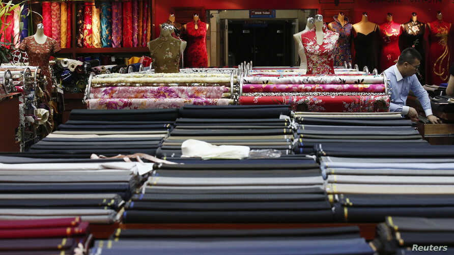 FILE - An employee works in a clothing shop in Beijing, China.