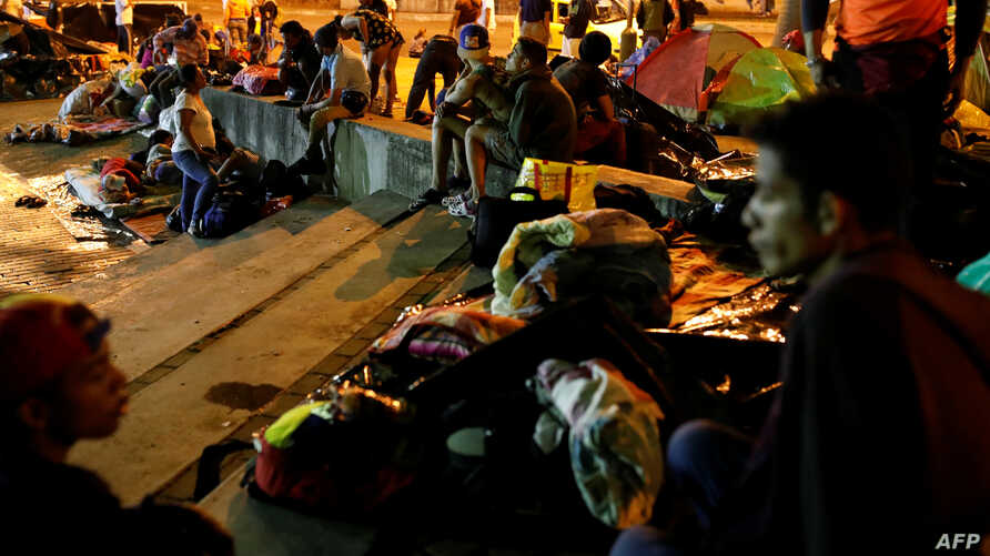 People prepare to sleep in a public square that has become an informal shelter for several hundred undocumented Venezuelan migrants in Bucaramanga, Colombia, Aug. 27, 2018.