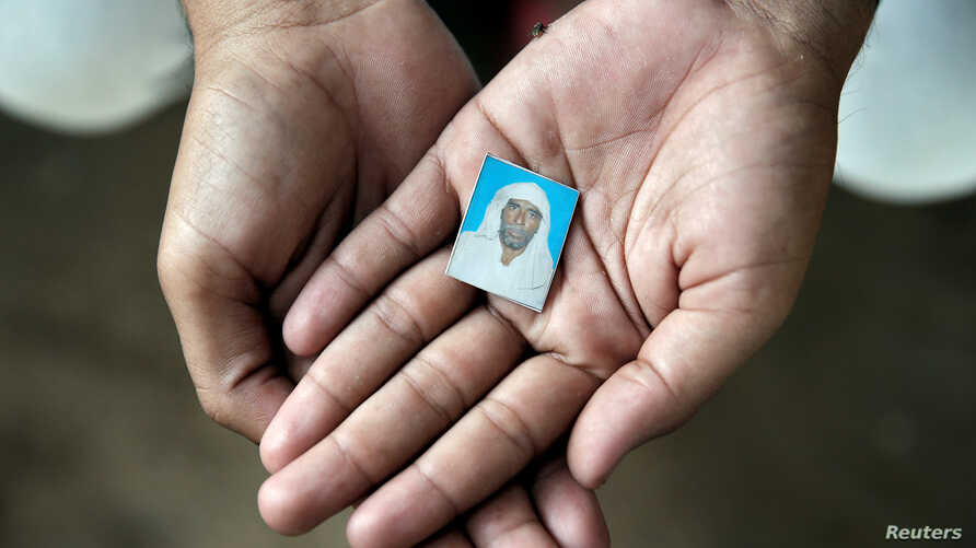FILE - Irshad Khan, 24, holds a picture of his late father Pehlu, 55, in Jaisinghpur, India, June 2, 2017.