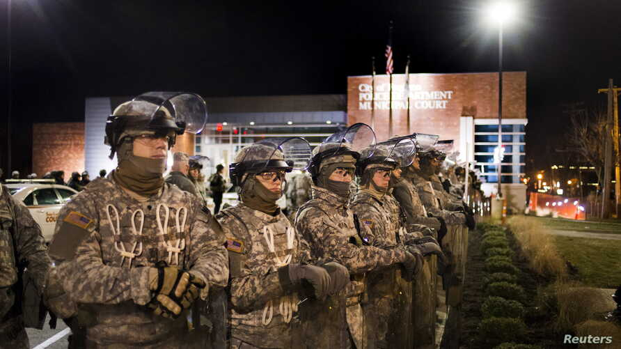 Members of the National Guard stand guard outside the Ferguson Police Department where demonstrators gathered to protest the shooting of Michael Brown in Ferguson, Mo., Nov. 28, 2014.