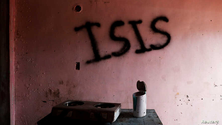 "Burned kitchen items are seen in front of a wall spray-painted with the word ""ISIS"" in a home in the most affected war-torn area of Marawi City, Lanao province, Philippines, May 11, 2019."