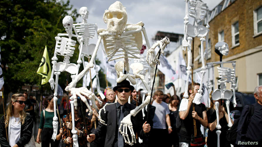 FILE - Extinction Rebellion activists march through East London, Britain, July 13, 2019.
