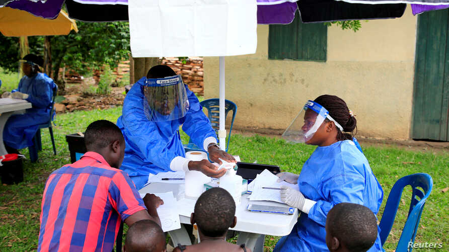 FILE - Ugandan health workers speak to civilians before carrying out the first vaccination exercise against the Ebola virus in Kirembo village, near the border with the Democratic Republic of Congo in Kasese district, Uganda, June 16, 2019.