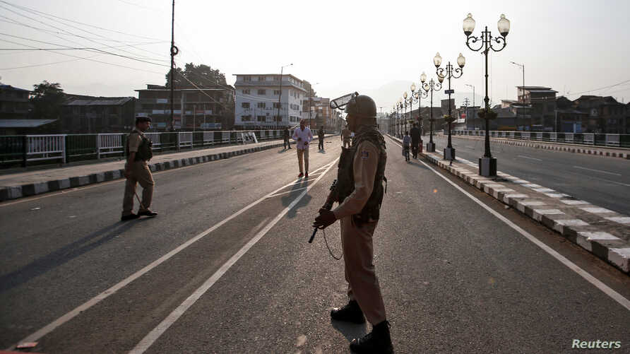 Indian security personnel stand guard on a deserted road during restrictions in Srinagar, Aug. 5, 2019.