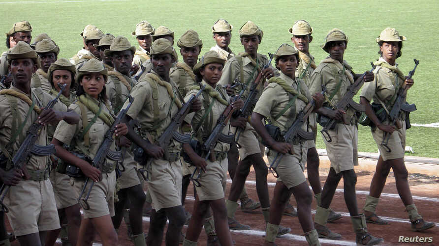 FILE - Eritrean soldiers march in Asmara, in May 2007.  Eritrea's conscription system forces young people to complete their final year of high school in the desert town of Sawa at a facility that's part school, part boot camp.