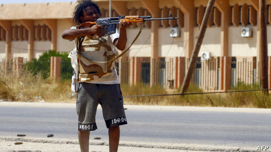 A fighter loyal to the U.N.-recognized Government of National Accord (GNA) points his gun toward enemy lines during clashes with forces loyal to strongman Khalifa Haftar, in Espiaa, south of the Libyan capital Tripoli, Aug. 21, 2019.