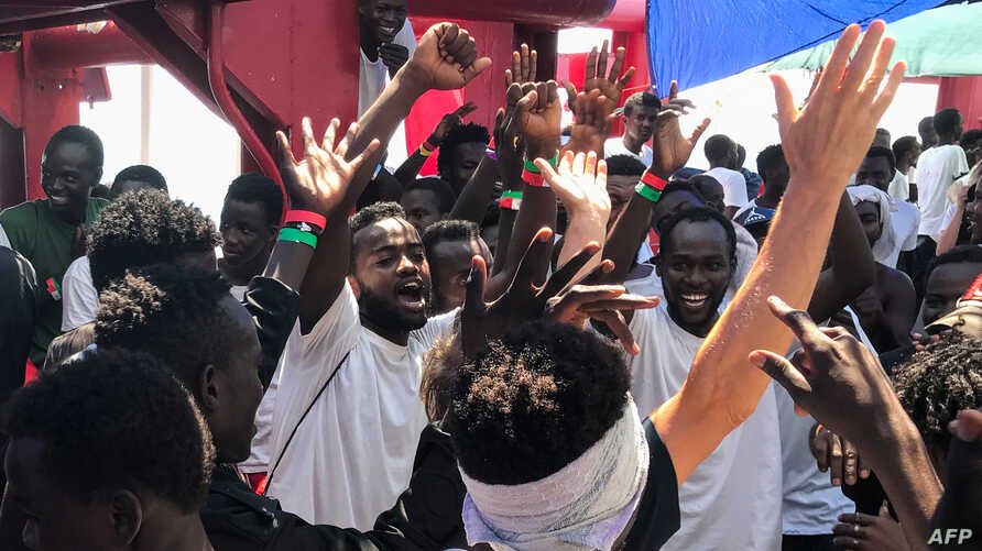 Migrants celebrate aboard the Ocean Viking rescue ship, jointly operated by French NGOs SOS Mediterranee and Medecins sans Frontieres (Doctors without Borders), Aug. 23, 2019, as six EU countries agreed to take them in after 14 days stranded at sea.