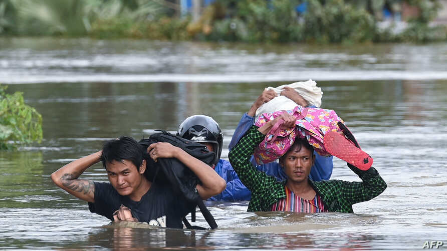 Residents evacuate as floodwaters submerged areas of Ye township in Mon State, Myanmar, Aug. 11, 2019.