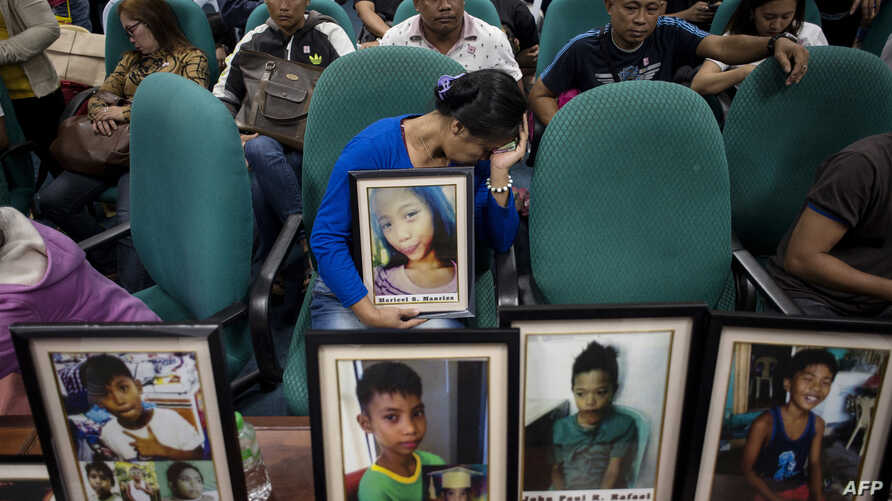 Parents of children injected with Dengvaxia vaccine carry pictures of their loved ones as they attend a senate hearing regarding the vaccine at the Senate building in Manila, Philippines, Feb. 21, 2018.