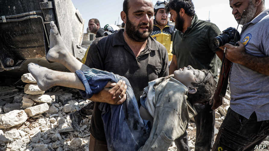 A Syrian carries the body of a child at the site of a reported regime airstrike on the village of Deir Sharqi on the eastern outskirts of Maaret al-Numan in Syria's northern province of Idlib, Aug. 17, 2019.