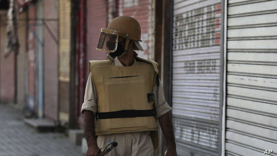 A Kashmiri policeman guards a closed shop in Srinagar, Indian-controlled Kashmir, Aug. 22, 2019.