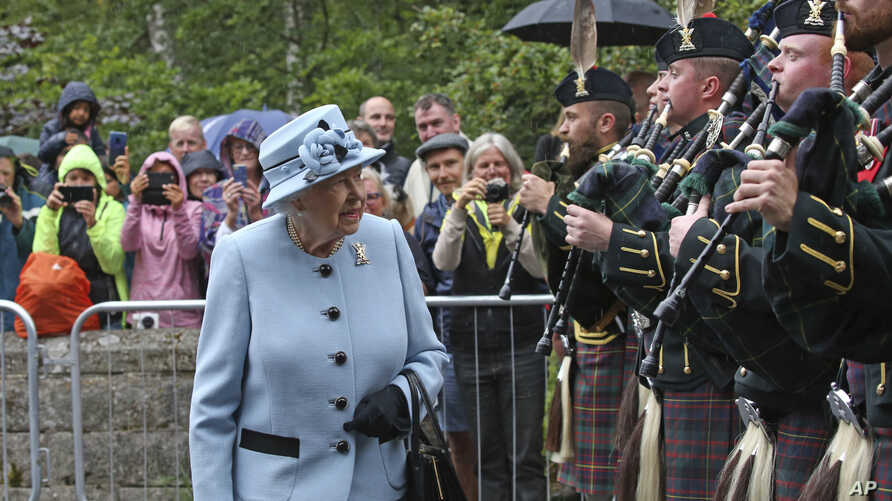 Queen Elizabeth II inspects the guard of honor before entering Balmoral Castle, Scotland, at the start of her annual holiday, Aug. 6, 2019.
