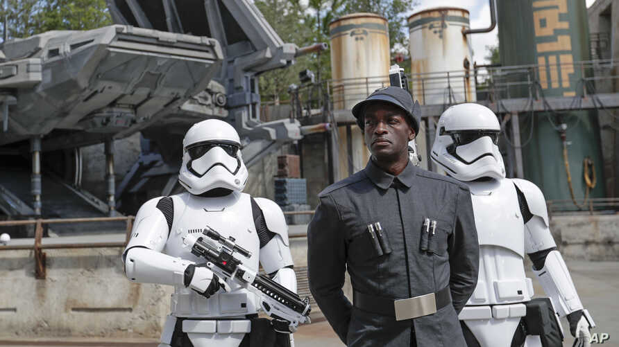 A First Order officer, center, and two storm troopers on patrol during a preview of the Star Wars-themed land, Galaxy's Edge in Hollywood Studios at Disney World, Aug. 27, 2019, in Lake Buena Vista, Florida.