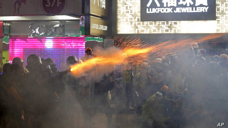 Policemen fire tear gas shells toward protesters at a shopping district of Hong Kong, Aug. 31, 2019.