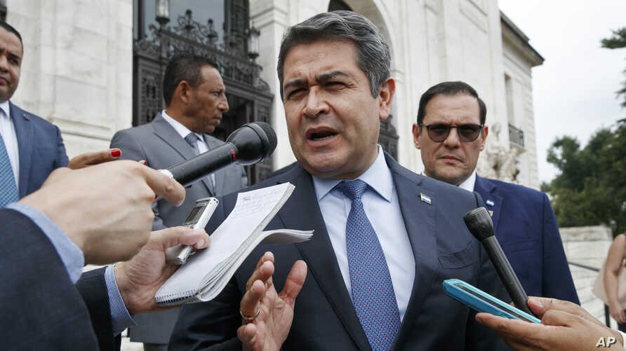 Honduran President Juan Orlando Hernandez answers questions from the Associated Press, Aug. 13, 2019, as he leaves a meeting at the Organization of American States, in Washington.