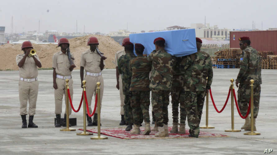 Members of a Somali military unit carry the body of Mogadishu Mayor Abdirahman Omar Osman for burial, in Mogadishu, Somalia, Aug. 4, 2019. Osman was killed in a suicide bombing July 24.