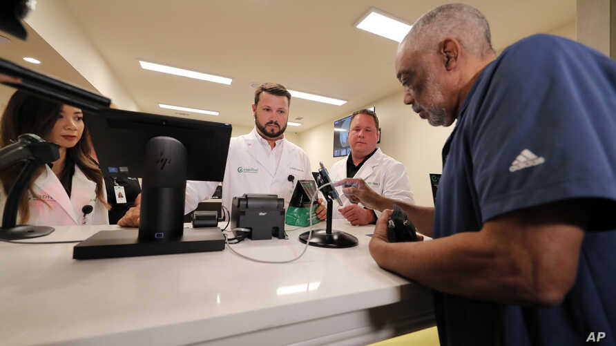 Alex Domino, right, the first ever person to legally receive medical marijuana in Louisiana, purchases his dose at Capitol Wellness Solutions, in Baton Rouge, Louisiana, Aug. 6, 2019.
