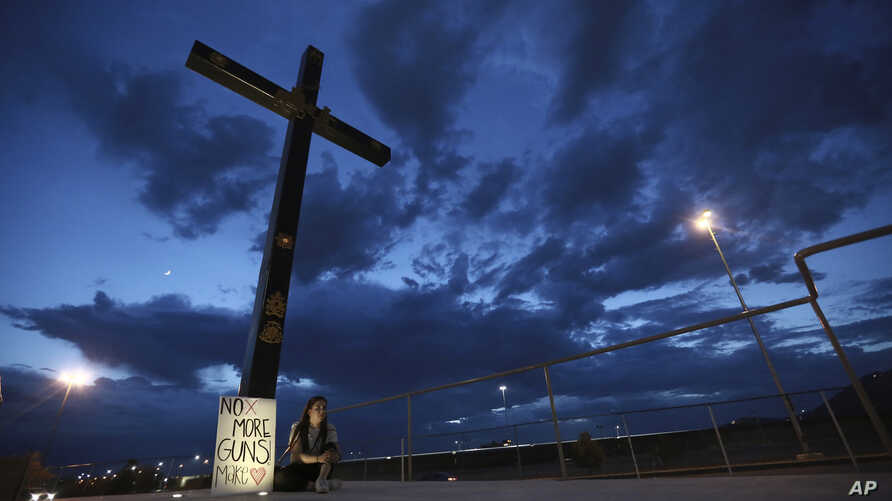 A woman sits next to a sign with a message that reads: ¨No More Guns! Make Love¨, in Juarez, Mexico, Aug. 3, 2019, where people are gathering for a vigil for the 3 Mexican nationals who were killed in an El Paso shopping-complex shooting.