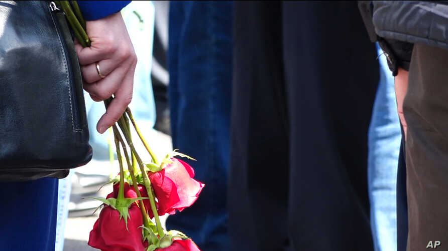In this grab taken from footage provided by the Russian State Atomic Energy Corporation ROSATOM press service, a woman holds roses as people gather for the funerals of five Russian nuclear engineers killed by a rocket explosion in Sarov, Aug. 12, 2019.