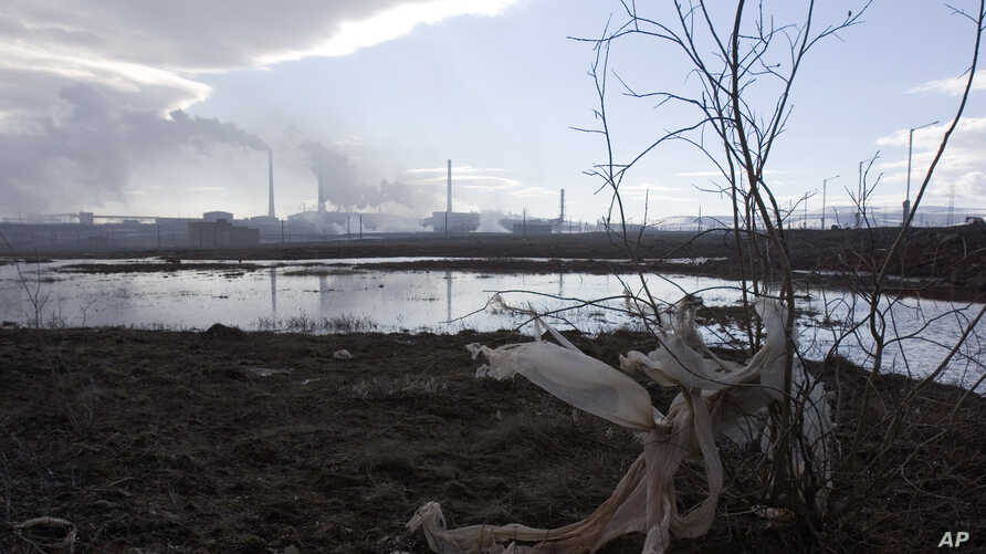 FILE - The Nadezhda nickel smelter pumps smoke over a pool of industrial water near the Arctic city of Norilsk, June 13, 2007.