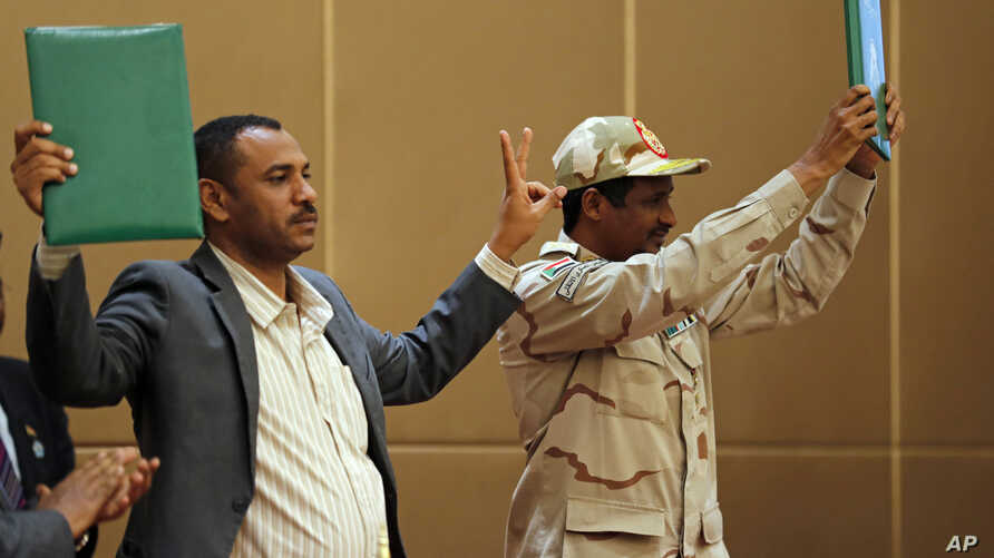 Gen. Mohamed Hamdan Daglo, the deputy head of the military council, right, and protest leader Ahmed Rabie hold up a signed agreement at a ceremony attended by African Union and Ethiopian mediators in the capital Khartoum, Sudan, August 4, 2019.