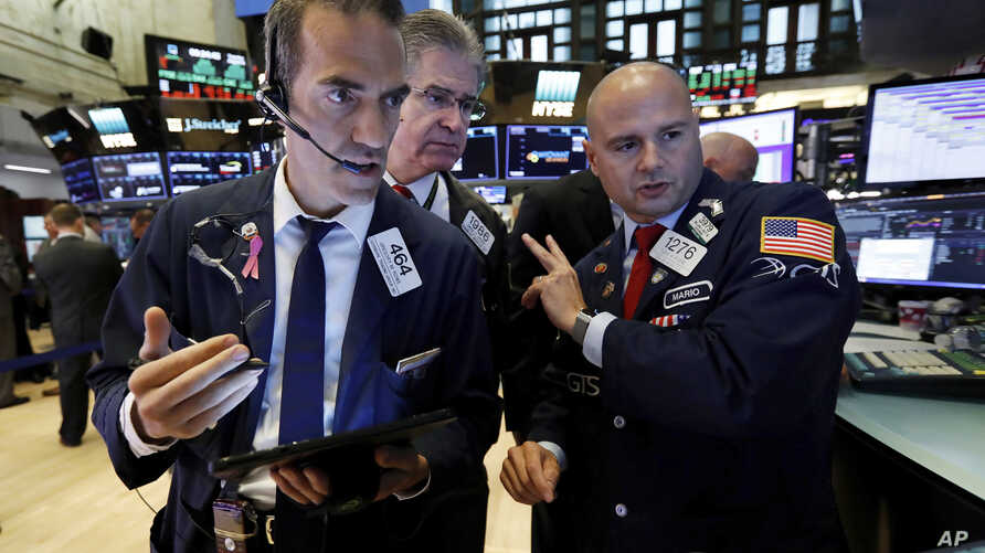 Traders Gregory Rowe, left, and Daniel Kryger, center, work with specialist Mario Picone on the floor of the New York Stock Exchange, Tuesday, Aug. 6, 2019.