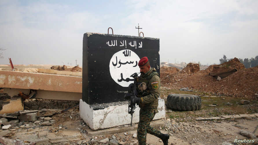 An Iraqi soldier walks next to a wall painted with the black flag commonly used by Islamic State militants, north of Mosul, Iraq, Jan. 21, 2017.