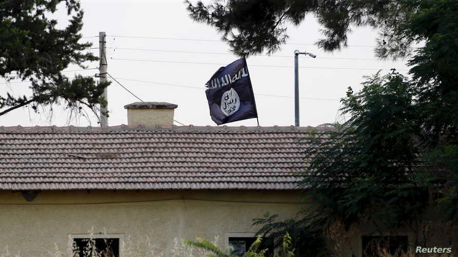 An Islamic State flag flies over a building in Syria's Jarablus as seen from the Turkish town of Karkamis, Turkey, Aug. 1, 2015.