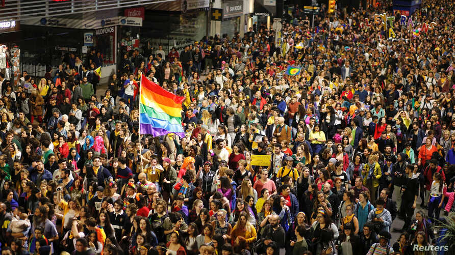 FILE - Members of the lesbian, gay, bisexual and transgender (LGBT) community and residents participate in the annual Diversity March in downtown Montevideo, Uruguay, Sept. 28, 2018.