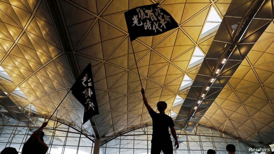 "Anti-extradition bill protesters wave flags with Chinese calligraphy that reads ""Liberate Hong Kong, the revolution of our times,"" at a mass demonstration at Hong Kong International Airport, in Hong Kong, China, Aug. 12, 2019."