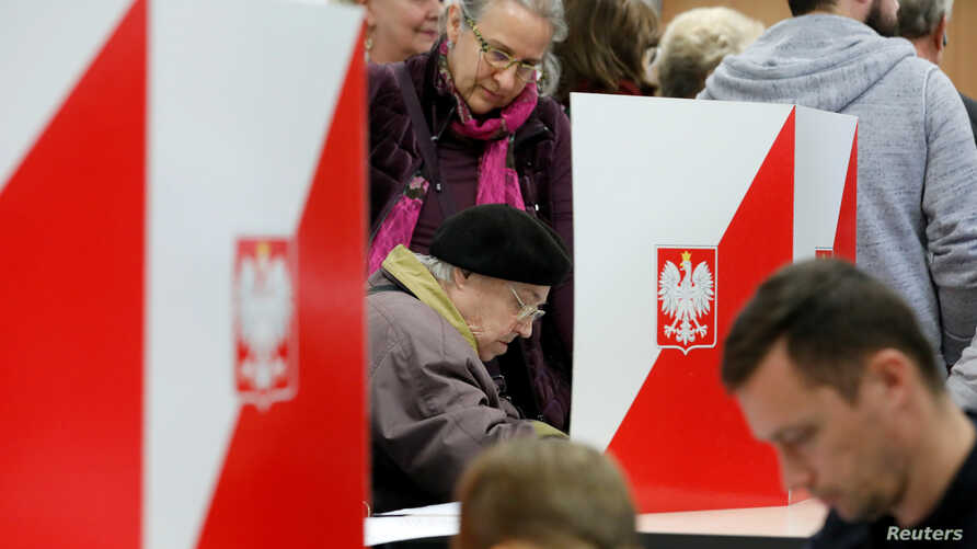 FILE - People attend the Polish regional elections, at a polling station in Warsaw, Poland, Oct. 21, 2018.
