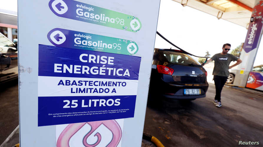 "A placard reading ""Energy crisis. Maximum limit 25 litres per filling"" is seen as a man fills up a car during a fuel strike, at a gas station near Lisbon, Portugal, Aug. 12, 2019."
