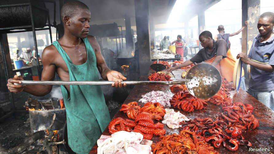 FILE - Tanzanian traders deep-fry freshly caught octopus at a market near the shores of the commercial capital Dar es Salaam, May 4, 2010.
