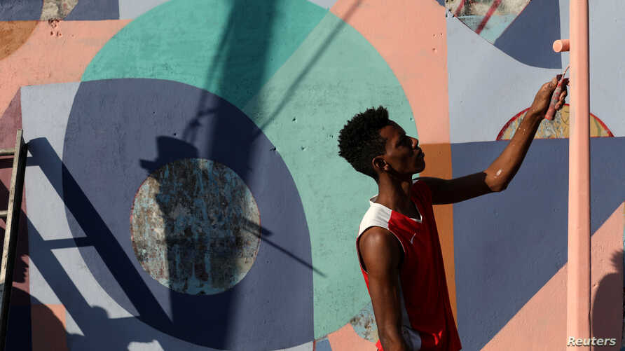 A community member helps to artist Fabian Solymar to paint a mural in a wall at the slum of Petare, in Caracas, Venezuela, Aug. 7, 2019.