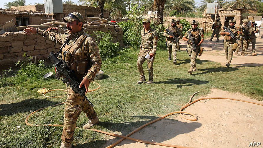 FILE - Iraq's rapid response forces storm a house in the Tarmiyah district, north of Baghdad, searching for wanted Islamic State group suspects, July 21, 2019. Iraq declared victory against IS in 2017, but the group continues to attack with sleeper cells.