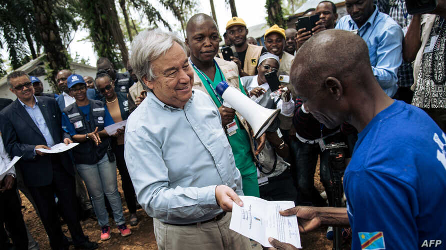 FILE - United Nations Secretary-General Antonio Guterres, left, hands a diploma to an Ebola survivor during a visit to an Ebola treatment center in Mangina, North Kivu province, Sept. 1, 2019.
