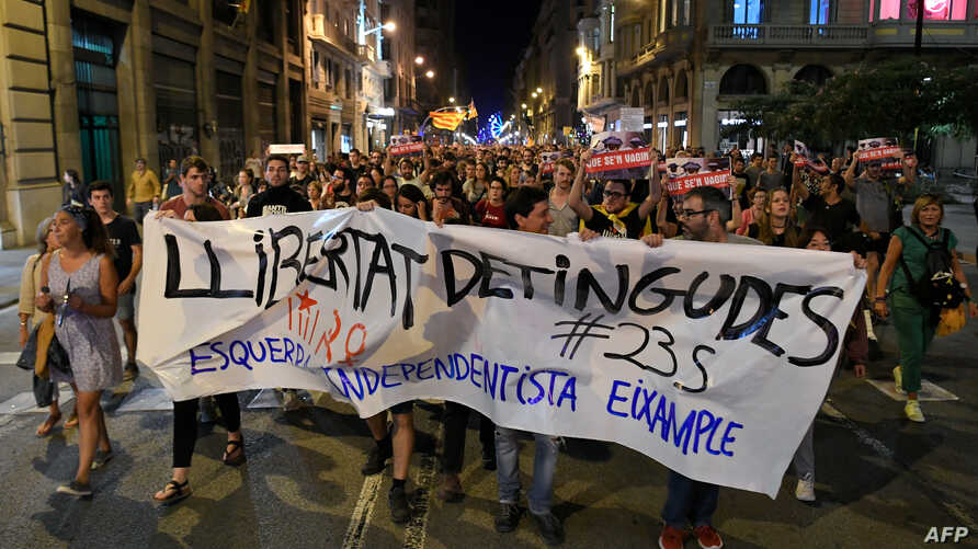 "People hold a banner reading ""release the prisoners"" as they walk towards the Catalonia¥s Police Headquarters, in Barcelona on September 26, 2019 during a demonstration to protest against the detention of seven radical militants for alleged belonging to a terrorist organization."