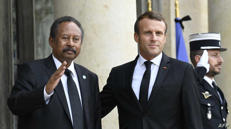 French President Emmanuel Macron, right, poses with Sudan's Prime Minister Abdalla Hamdok ahead of a meeting at The Elysee Presidential Palace in Paris, Sept. 30, 2019.