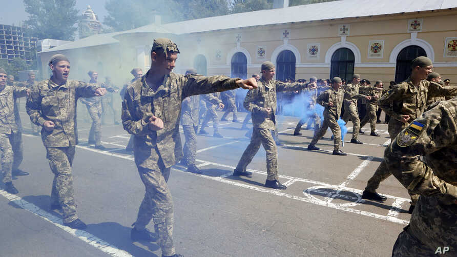 FILE - Graduate cadets give a demonstration during a graduation ceremony at the military lyceum in Kyiv, Ukraine, May 31, 2019.